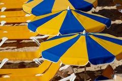 与等待游人,在海滩的有偿的服务的阳伞和椅子的拥挤海滩 免版税库存照片