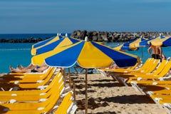 与等待游人,在海滩的有偿的服务的阳伞和椅子的拥挤海滩 免版税图库摄影