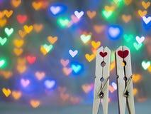与红心形状的逗人喜爱的木晒衣夹在华伦泰的美好的心形的bokeh背景 库存图片