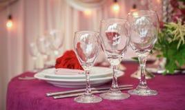 与红色花、餐巾、葡萄酒利器、玻璃和蜡烛,明亮的夏天桌装饰的欢乐婚姻的桌设置 库存图片