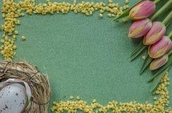与红yellowk郁金香和鸡蛋的复活节背景在与拷贝空间的绿色闪烁背景 免版税图库摄影