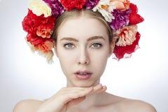 与纤巧明亮的秀丽的女性模型,有五颜六色的花装饰诗歌选在她的头的 免版税图库摄影