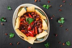 与烤干酪辣味玉米片或皮塔饼芯片的豆沙,胡椒和绿色在板材在黑暗的背景 墨西哥快餐,素食食物,顶视图 库存图片