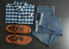 与牛仔裤、衬衣、玻璃和鞋子的平的被放置的构成 免版税图库摄影