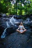 与瀑布的年轻女人实践的瑜伽在背景 免版税库存图片