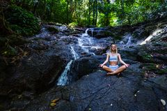与瀑布的年轻女人实践的瑜伽在背景 免版税库存照片