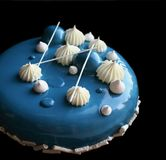 与白色巧克力和镜子釉的蓝色和白蛋糕在黑背景 免版税库存图片