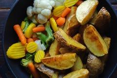 与菜的被烘烤的土豆在平底锅 顶视图 免版税库存图片