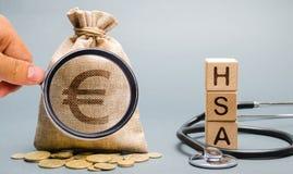 与词有的木块和与听诊器的金钱袋子 健康储蓄帐户 胳膊关心健康查出滞后 健康保险 投资 免版税图库摄影