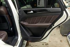 与豪华非常昂贵的新的白色奔驰车GLE小轿车AMG 63s汽车立场的后门的内部看法在洗涤的箱子的 免版税库存图片