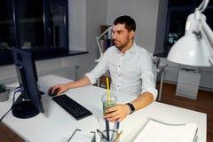 与运转在夜办公室的计算机的商人 库存图片