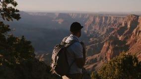 与远足在度假的背包的慢动作愉快的年轻商人在大峡谷史诗夏天日落全景  股票视频