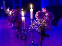 与蜡烛和花的被盖的婚姻的桌 免版税库存照片