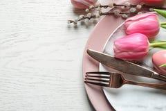 与花的欢乐复活节桌设置在木背景,在看法上 图库摄影