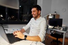 与膝上型计算机工作的商人在夜办公室 免版税库存照片