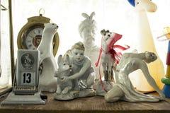 与老苏联小雕象的一个架子:有狗的一个男孩,芭蕾舞女演员,狡猾的人,胸象 免版税库存照片