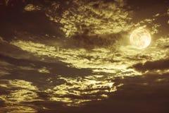 与黑暗多云的美丽的夜空 有些云彩给满月投上阴影 免版税库存图片
