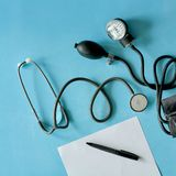 与黑笔和phonendoscope听诊器,在蓝色背景的血压计的白色板料纸 免版税库存照片