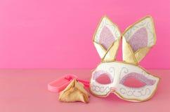 与逗人喜爱的兔子面具、发出大声音的人和hamantash曲奇饼的普珥节庆祝概念犹太狂欢节假日在木桌 免版税库存图片