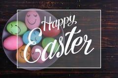 与逗人喜爱的面孔的复活节彩蛋在板材 为在厨房用桌上的假日做准备,在黑暗的背景 文本,复活节快乐 库存照片
