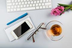 与键盘、电话、文字供应和花的白色办公桌桌 图库摄影