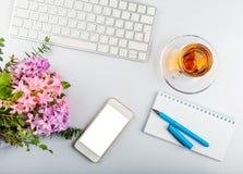 与键盘、电话、文字供应和花的白色办公桌桌 免版税库存图片