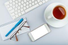 与键盘,智能手机,茶的办公桌桌 免版税库存图片