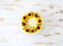 与mascarpone的美丽的生日快乐蛋糕装饰用莓、开心果和蜡烛在蛋糕立场 免版税图库摄影