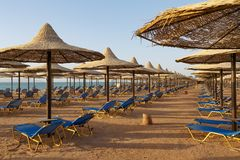 与sunbeds的海滩在海滨的秸杆沙滩伞下 免版税图库摄影