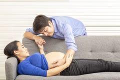 丈夫和妻子怀孕的 孕妇和丈夫微笑画象  父亲是怀孕的母亲的胃 年轻未来 库存图片