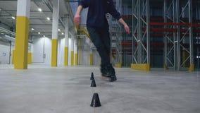专业四轮溜冰者在后勤学中心的做障碍滑雪慢动作 股票录像