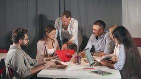 专家在业务会议在年轻公司中谈论想法和报告 股票录像