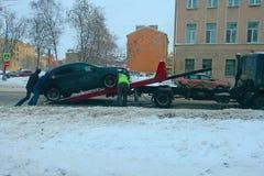 三个人在拖车装载一辆汽车 免版税库存图片