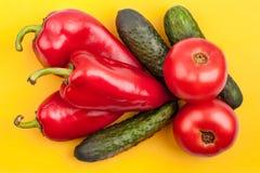 三个明亮的红辣椒、三个绿色黄瓜和两个红色蕃茄在黄色背景顶视图关闭 图库摄影