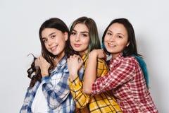 三个时髦的女孩最好的朋友 一起站立和获得乐趣 查看照相机 在灰色背景 免版税库存图片
