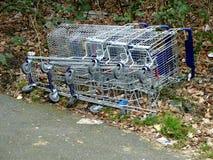 下落和放置在地面上的杂货推车 空的超级市场的概念,销售量下降,关闭超级市场分支 库存照片