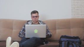 一个中间年迈的人坐沙发在他旁边使用一手提电脑,是一个大旅游背包 股票录像