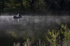 一个人在河钓鱼 有薄雾的早晨夏天 免版税库存图片