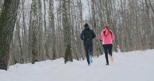 一个人和妇女奔跑在公园在冬天,实践一种健康生活方式和交往以他们的在的健康 股票录像
