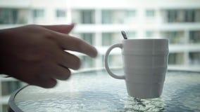 一个人的手的特写镜头采取一份热的饮料的一个杯子从桌的 免版税库存图片