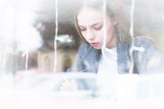 一个可爱的年轻新闻工作者在咖啡馆的女孩和笔记薄的画象有笔的在陈列室后 非对比视图 免版税库存图片