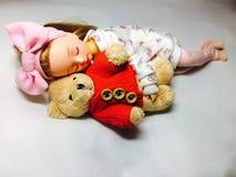 一个可爱的日本玩偶与她的玩具熊睡觉 库存照片