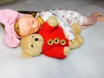 一个可爱的日本玩偶与她的玩具熊睡觉 库存图片