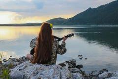 一个女孩的剪影弹吉他的日落的由河 免版税库存照片