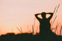 一个女孩的剪影有日落的 库存图片