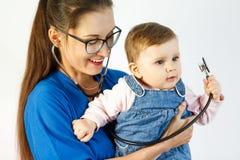 一个小孩子在拿着听诊器的医生的手上 免版税库存图片
