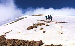 一个小组游人攀登岩石积雪的山腰对它有雾的山顶 免版税库存照片