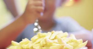 一个小男孩的画象吃在咖啡馆的土豆油炸物 股票视频