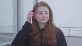 一个年轻逗人喜爱的女孩的画象有红色头发的在一个房子的屋顶或大阳台的一个黑暗的外套身分冷的,有风 影视素材