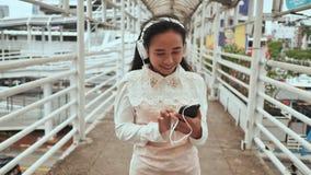 一个快乐的印度尼西亚女孩在一座桥梁站立在白色耳机的城市并且选择在她的智能手机的音乐 影视素材